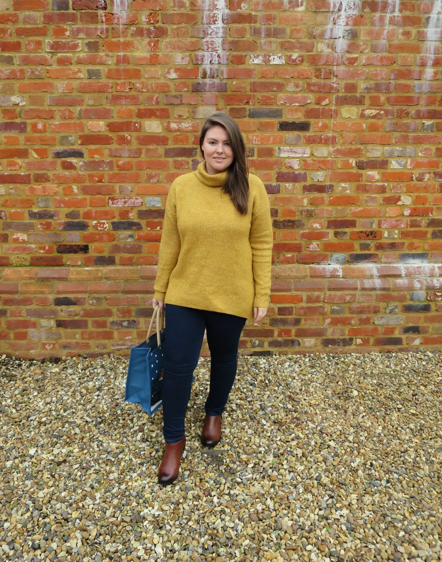 Me standing by a brick wall wearing a mustard jumper, jeans and my Vionic Shoes